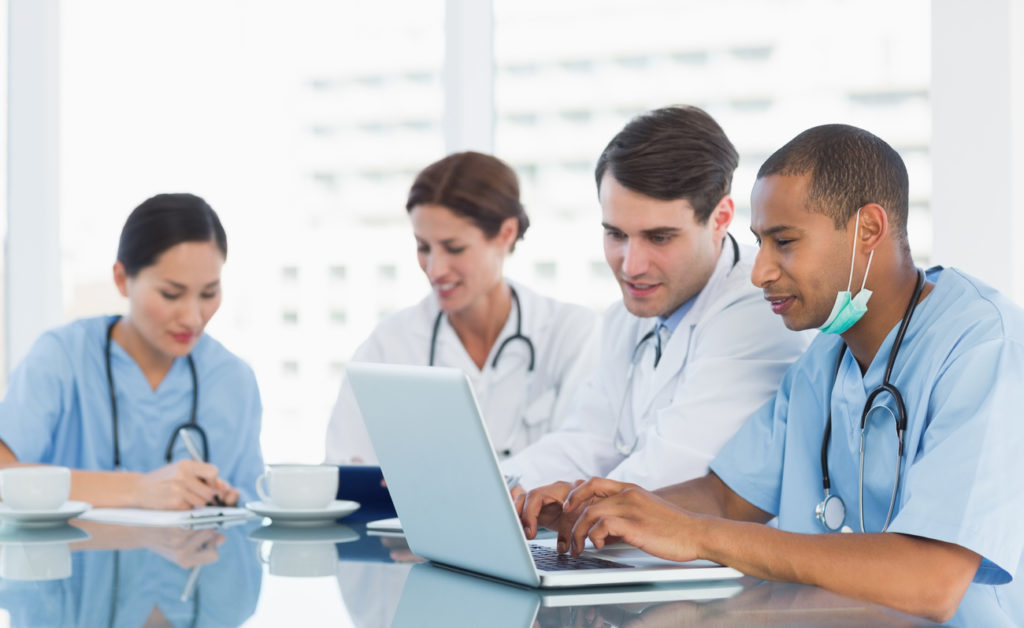 A group of doctors sit at a table, discussing HIPAA compliance in medical tech solutions.