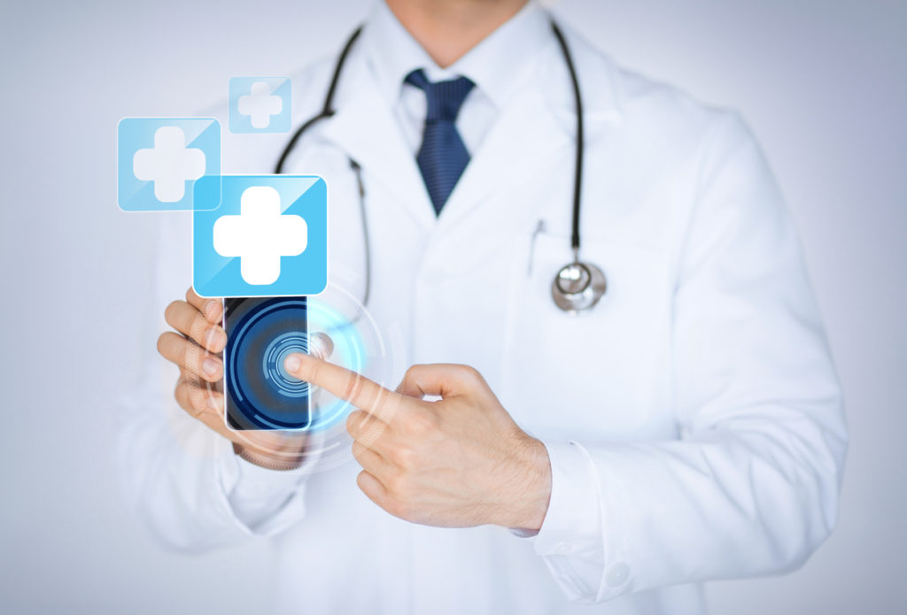 A doctor holding a smartphone, pointing to its screen, where healthcare apps would appear.