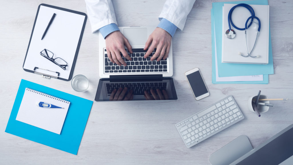 A doctor sits at his desk surrounded technology (laptop, keyboard, smartphone, tablet). HIPAA compliance can be tricky but it is part of an effective medical marketing strategy.