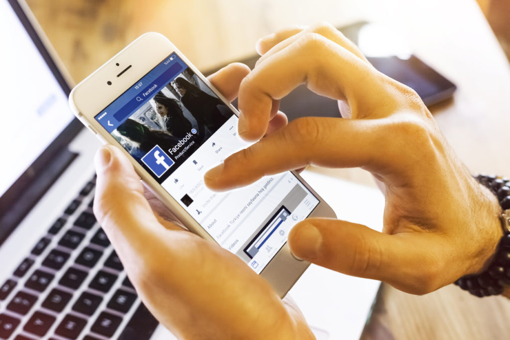 A person holds and phone with a laptop keyboard in the background, using social media for clinical trial recruitment.